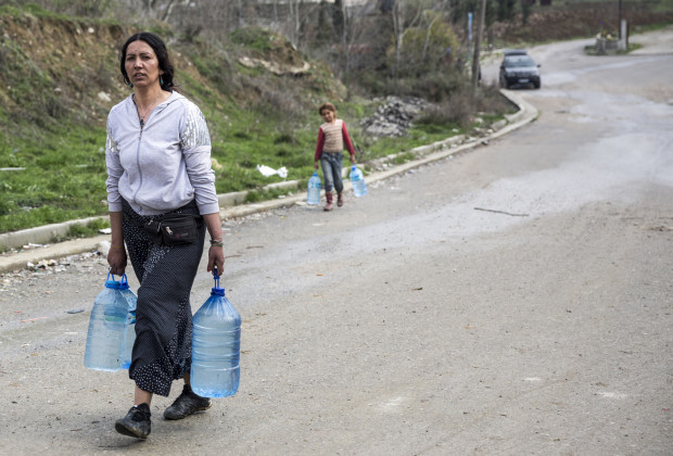 A woman and her daughter carry drinking water, which they must buy, to Liqeni Roma camp in Tirana, Albania, one of the poorest settlements in the city.  PHOTO BY JODI HILTON