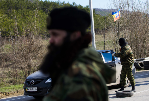 Member of a Serbian Chetnik paramilitary group man a checkpoint on the highway between Simferopol and Sevastopol in the Crimean peninsular March 13, 2014. Serbian paramilitaries have offered their help to pro-Russian self-defence volunteers who set up road blocks on the main road to the Crimean port city of Sevastopol, home to the Russian Black Sea fleet. Road blocks were set up last week when pro-Russian men in green uniforms without insignia started appearing outside bases taking control of naval and military installations in Crimea. REUTERS/Thomas Peter (UKRAINE  - Tags: POLITICS MILITARY CIVIL UNREST) - RTR3GYLN