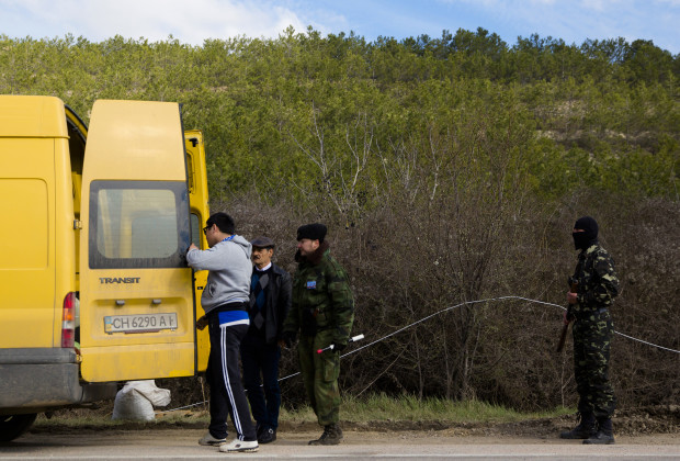A member of a local self-defence unit (R) and a member of a Serbian Chetnik paramilitary group check a van at a checkpoint on the highway between Simferopol and Sevastopol in the Crimean peninsular March 13, 2014. Serbian paramilitaries have offered their help to pro-Russian self-defence volunteers who set up road blocks on the main road to the Crimean port city of Sevastopol, home to the Russian Black Sea fleet. Road blocks were set up last week when pro-Russian men in green uniforms without insignia started appearing outside bases taking control of naval and military installations in Crimea. REUTERS/Thomas Peter (UKRAINE  - Tags: CIVIL UNREST MILITARY POLITICS) - RTR3GYNP