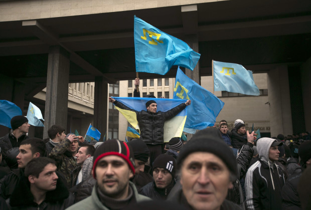 Crimean Tatars hold flags during rallies near the Crimean parliament building in Simferopol February 26, 2014. Thousands of pro-Russia separatists tussled with supporters of Ukraine's new leaders in Crimea on Wednesday as tempers boiled over the future of the region following the upheaval that swept away President Viktor Yanukovich. One person died, apparently of a heart attack, and two others were trampled and injured when people stumbled and fell to the ground in the crush, witnesses said. REUTERS/Baz Ratner (UKRAINE - Tags: POLITICS CIVIL UNREST) - RTR3FQXI