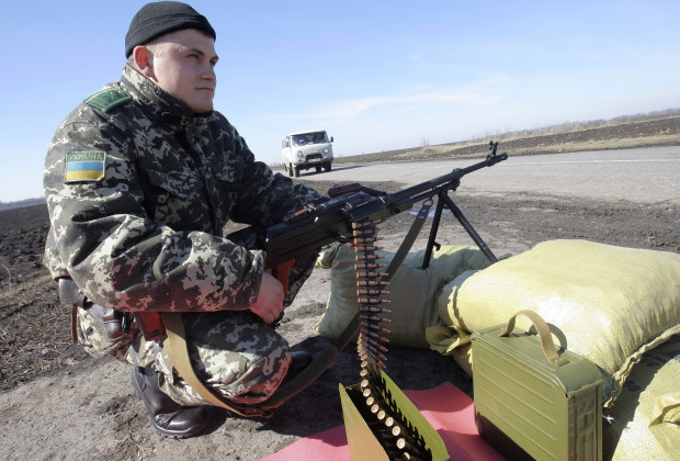 A Ukrainian soldier mans a checkpoint close to the Russian border near the Ukrainian city of Kharkiv March 21, 2014. Russian shares fell sharply on Friday as investors took fright at tougher than expected U.S. sanctions against President Vladimir Putin's inner circle over Moscow's seizure of Crimea from Ukraine. REUTERS/Stringer (UKRAINE  - Tags: POLITICS MILITARY) - RTR3I1E5