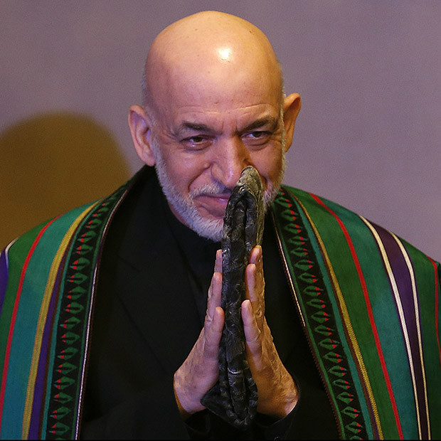 Afghanistan's President Hamid Karzai gestures as he arrives at a news conference on March 6, 2014.