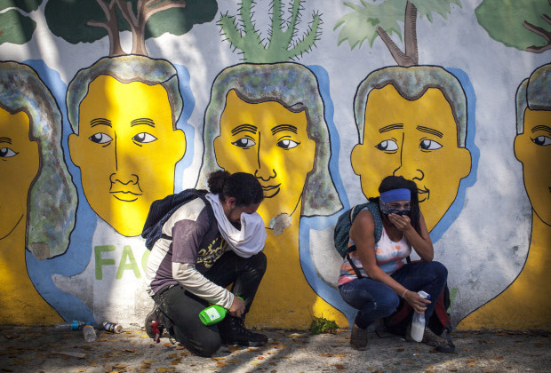 March 12th, 2014. Caracas.  Protesters overcome by the gas shelters behind a mural. One month after student protests over violence, inflation and food shortages convulsed Venezuela, resulting in the deaths of 3 people on that first day of unrest alone, thousands of students took to the streets in Caracas on Wednesday morning in parallel rallies, one to support the government, the other condemning this month's violence against protesters and continuing to call for change. At least 3,0000 students attempted to march to the offices of the government Public Defender's offices in Caracas to protest allegations of torture of detained protesters. National police blocked the students exit from the Central University of Venezuela, and after negotiations failed, the students attempted to push through the police lines, and were met with water canons, tear gas, and bird shot.