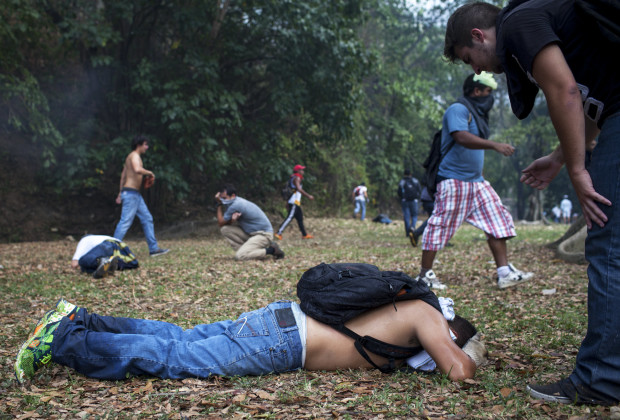 March 12th, 2014. Caracas. A student overcome by gas lays on the ground. One month after student protests over violence, inflation and food shortages convulsed Venezuela, resulting in the deaths of 3 people on that first day of unrest alone, thousands of students took to the streets in Caracas on Wednesday morning in parallel rallies, one to support the government, the other condemning this month's violence against protesters and continuing to call for change. At least 3,0000 students attempted to march to the offices of the government Public Defender's offices in Caracas to protest allegations of torture of detained protesters. National police blocked the students exit from the Central University of Venezuela, and after negotiations failed, the students attempted to push through the police lines, and were met with water canons, tear gas, and bird shot.