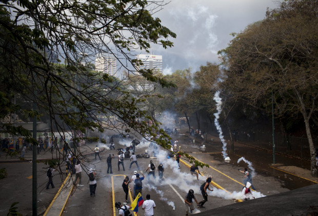 March 12th, 2014. Caracas. From an archway, the protesters are seen amid a rain of gas. One month after student protests over violence, inflation and food shortages convulsed Venezuela, resulting in the deaths of 3 people on that first day of unrest alone, thousands of students took to the streets in Caracas on Wednesday morning in parallel rallies, one to support the government, the other condemning this month's violence against protesters and continuing to call for change. At least 3,0000 students attempted to march to the offices of the government Public Defender's offices in Caracas to protest allegations of torture of detained protesters. National police blocked the students exit from the Central University of Venezuela, and after negotiations failed, the students attempted to push through the police lines, and were met with water canons, tear gas, and bird shot.