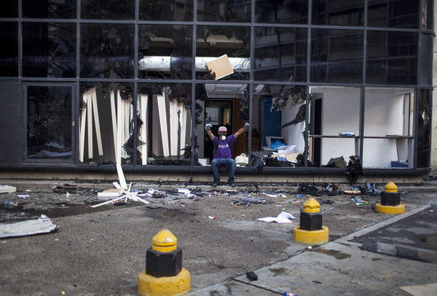 March 12th, 2014. Caracas. A protester poses in the broken windows of a looted office building in Altamira. One month after student protests over violence, inflation and food shortages convulsed Venezuela, resulting in the deaths of 3 people on that first day of unrest alone, thousands of students took to the streets in Caracas on Wednesday morning in parallel rallies, one to support the government, the other condemning this month's violence against protesters and continuing to call for change. At least 3,0000 students attempted to march to the offices of the government Public Defender's offices in Caracas to protest allegations of torture of detained protesters. National police blocked the students exit from the Central University of Venezuela, and after negotiations failed, the students attempted to push through the police lines, and were met with water canons, tear gas, and bird shot.
