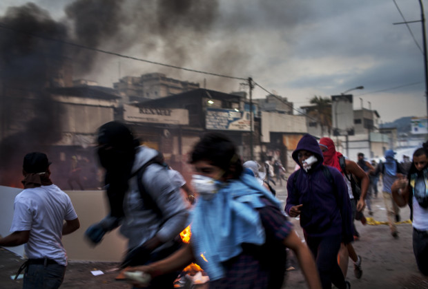 March 12th, 2014. Caracas. Protesters in Altamira run as National Guardsmen advance with water canons. One month after student protests over violence, inflation and food shortages convulsed Venezuela, resulting in the deaths of 3 people on that first day of unrest alone, thousands of students took to the streets in Caracas on Wednesday morning in parallel rallies, one to support the government, the other condemning this month's violence against protesters and continuing to call for change. At least 3,0000 students attempted to march to the offices of the government Public Defender's offices in Caracas to protest allegations of torture of detained protesters. National police blocked the students exit from the Central University of Venezuela, and after negotiations failed, the students attempted to push through the police lines, and were met with water canons, tear gas, and bird shot.