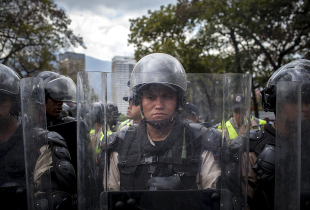 March 12th, 2014. Caracas. National Police await the students barring their exit from the campus for the unsanctioned protest. One month after student protests over violence, inflation and food shortages convulsed Venezuela, resulting in the deaths of 3 people on that first day of unrest alone, thousands of students took to the streets in Caracas on Wednesday morning in parallel rallies, one to support the government, the other condemning this month's violence against protesters and continuing to call for change. At least 3,0000 students attempted to march to the offices of the government Public Defender's offices in Caracas to protest allegations of torture of detained protesters. National police blocked the students exit from the Central University of Venezuela, and after negotiations failed, the students attempted to push through the police lines, and were met with water canons, tear gas, and bird shot.