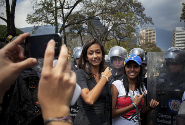 March 12th, 2014. Caracas. Two students pose for a phone photo with the line of police as they await a decision on whether they will be allowed to continue. One month after student protests over violence, inflation and food shortages convulsed Venezuela, resulting in the deaths of 3 people on that first day of unrest alone, thousands of students took to the streets in Caracas on Wednesday morning in parallel rallies, one to support the government, the other condemning this month's violence against protesters and continuing to call for change. At least 3,0000 students attempted to march to the offices of the government Public Defender's offices in Caracas to protest allegations of torture of detained protesters. National police blocked the students exit from the Central University of Venezuela, and after negotiations failed, the students attempted to push through the police lines, and were met with water canons, tear gas, and bird shot.