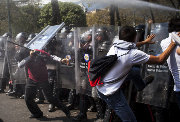 March 12th, 2014. Caracas. Protesters rush the police lines when they are not permitted to pass, and are met with pepper spray and water canons.  One month after student protests over violence, inflation and food shortages convulsed Venezuela, resulting in the deaths of 3 people on that first day of unrest alone, thousands of students took to the streets in Caracas on Wednesday morning in parallel rallies, one to support the government, the other condemning this month's violence against protesters and continuing to call for change. At least 3,0000 students attempted to march to the offices of the government Public Defender's offices in Caracas to protest allegations of torture of detained protesters. National police blocked the students exit from the Central University of Venezuela, and after negotiations failed, the students attempted to push through the police lines, and were met with water canons, tear gas, and bird shot.