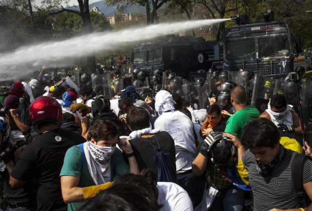 March 12th, 2014. Caracas. As the students press forward they are met with water canons and gas. One month after student protests over violence, inflation and food shortages convulsed Venezuela, resulting in the deaths of 3 people on that first day of unrest alone, thousands of students took to the streets in Caracas on Wednesday morning in parallel rallies, one to support the government, the other condemning this month's violence against protesters and continuing to call for change. At least 3,0000 students attempted to march to the offices of the government Public Defender's offices in Caracas to protest allegations of torture of detained protesters. National police blocked the students exit from the Central University of Venezuela, and after negotiations failed, the students attempted to push through the police lines, and were met with water canons, tear gas, and bird shot.