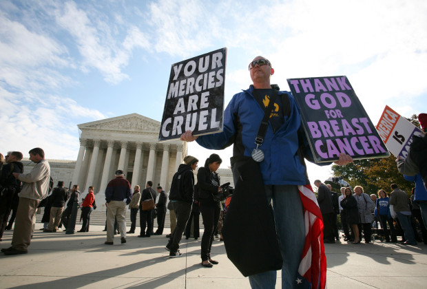 """Timothy Phelps, a member of the Westboro Baptist Church from Topeka, Kansas, stands with banners in front of the US Supreme Court October 6, 2010 in Washington,DC. The Supreme Court Wednesday will examine whether the right to free speech protects a controversial religious group that pickets military funerals displaying signs that read: """"Thank God for dead soldiers."""" The Kansas-based Westboro Baptist Church has for years disrupted the funerals of US soldiers killed in Iraq and Afghanistan, claiming the wars are divine punishment because the United States tolerates gays, including in the military. AFP/PHOTO Kimihiro Hoshino (Photo credit should read KIMIHIRO HOSHINO/AFP/Getty Images)"""