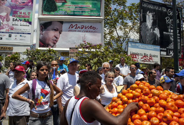 March 12th, 2014. Caracas. A vendor sells oranges to student protesters beneath a Maduro billboard. One month after student protests over violence, inflation and food shortages convulsed Venezuela, resulting in the deaths of 3 people on that first day of unrest alone, thousands of students took to the streets in Caracas on Wednesday morning in parallel rallies, one to support the government, the other condemning this month's violence against protesters and continuing to call for change. At least 3,0000 students attempted to march to the offices of the government Public Defender's offices in Caracas to protest allegations of torture of detained protesters. National police blocked the students exit from the Central University of Venezuela, and after negotiations failed, the students attempted to push through the police lines, and were met with water canons, tear gas, and bird shot.