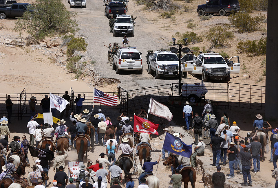 Protesters gather at the Bureau of Land Management's base camp, where cattle that were seized from rancher Cliven Bundy are being held, near Bunkerville, Nevada April 12, 2014. The U.S. Bureau of Land Management on Saturday said it had called off an effort to round up Bundy's herd of cattle that it had said were being illegally grazed in southern Nevada, citing concerns about safety. The conflict between Bundy and U.S. land managers had brought a team of armed federal rangers to Nevada to seize the 1,000 head of cattle.