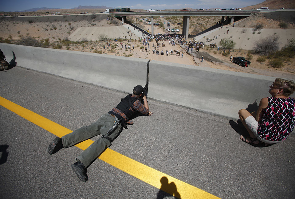 Eric Parker from central Idaho aims his weapon from a bridge as protesters gather by the Bureau of Land Management's base camp, where cattle that were seized from rancher Cliven Bundy are being held, near Bunkerville, Nevada April 12, 2014. The U.S. Bureau of Land Management on Saturday said it had called off an effort to round up Bundy's herd of cattle that it had said were being illegally grazed in southern Nevada, citing concerns about safety. The conflict between Bundy and U.S. land managers had brought a team of armed federal rangers to Nevada to seize the 1,000 head of cattle.