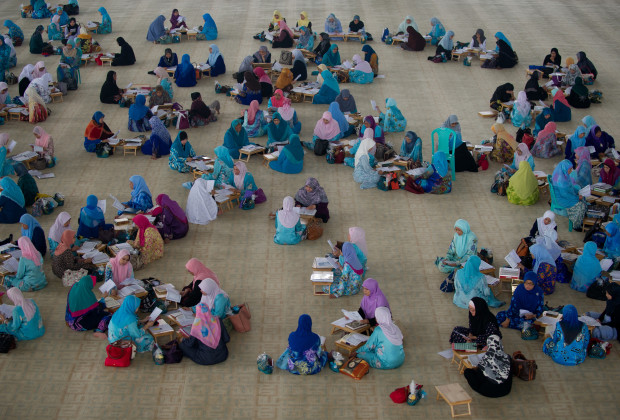 "Malaysian Muslim women read the Koran inside a mosque during Al-Quran recital and graduation ceremony in Putrajaya, outside Kuala Lumpur on August 1, 2013. Muslims recite the Koran on the last eight days of Ramadan which is described in the Koran as ""Lailatul Qadar"" - ""a night better than a thousand months"".     AFP PHOTO / MOHD RASFAN        (Photo credit should read MOHD RASFAN/AFP/Getty Images)"