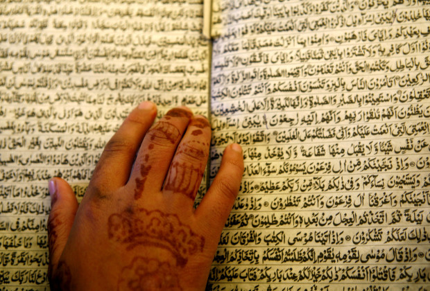 A young Kashmiri woman, with traditional Muslim henna tattoos marking the end of 'amadan and the celebration of Eid, reads the Koran in a tent serving as an Islamic school in the relief camp of Mehnaj near the earthquake-devastated city of Muzaffarabad in Pakistan-administered Kashmir January 19, 2006. More than two million people have been living in tents or crude shelters patched together from ruined homes since the Oct. 8 quake killed more than 73,000 people in northern Pakistan. REUTERS/Yannis Behrakis - RTR18H31