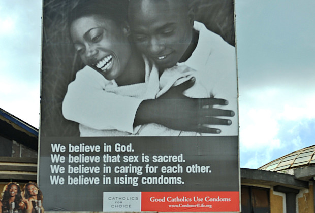 "A couple walks by a billboard promoting the use of condoms by a US-based Catholic group calling itself ""Catholics for choice"" in Nairobi on May 9, 2013. Kenya's Roman Catholic Church has condemned the Catholic group for the billboard and newspaper advertising campaign promoting condom use.     AFP PHOTO/Tony KARUMBA        (Photo credit should read TONY KARUMBA/AFP/Getty Images)"