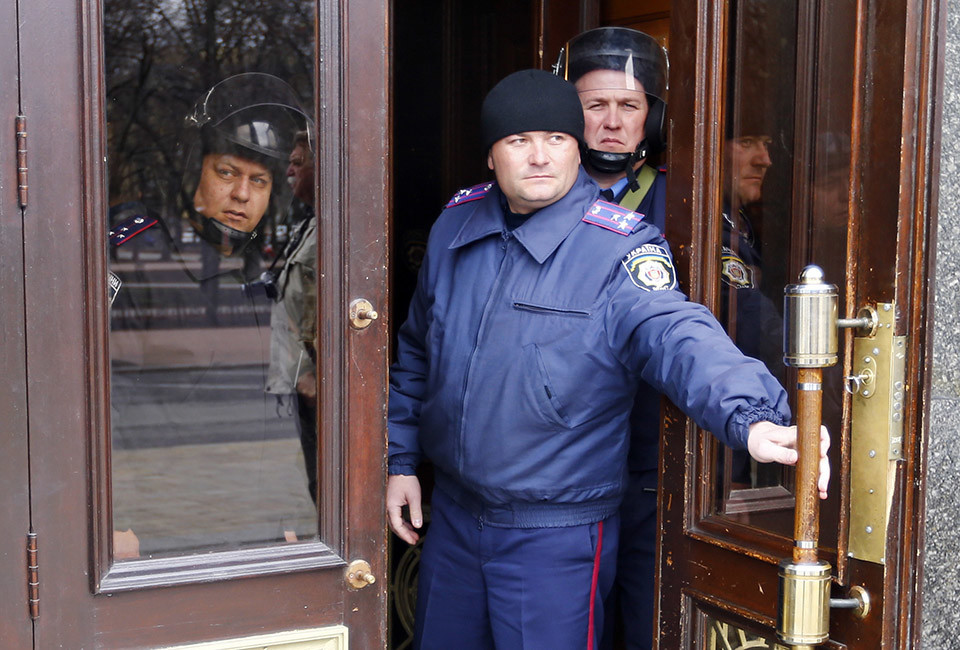 Interior Ministry members look out from the entrance of the regional administration headquarters in Luhansk, in eastern Ukraine April 14, 2014. Ukraine's president on Monday threatened military action after pro-Russian separatists occupying government buildings in the east ignored an ultimatum to leave and another group of rebels attacked a police headquarters in the troubled region.2H