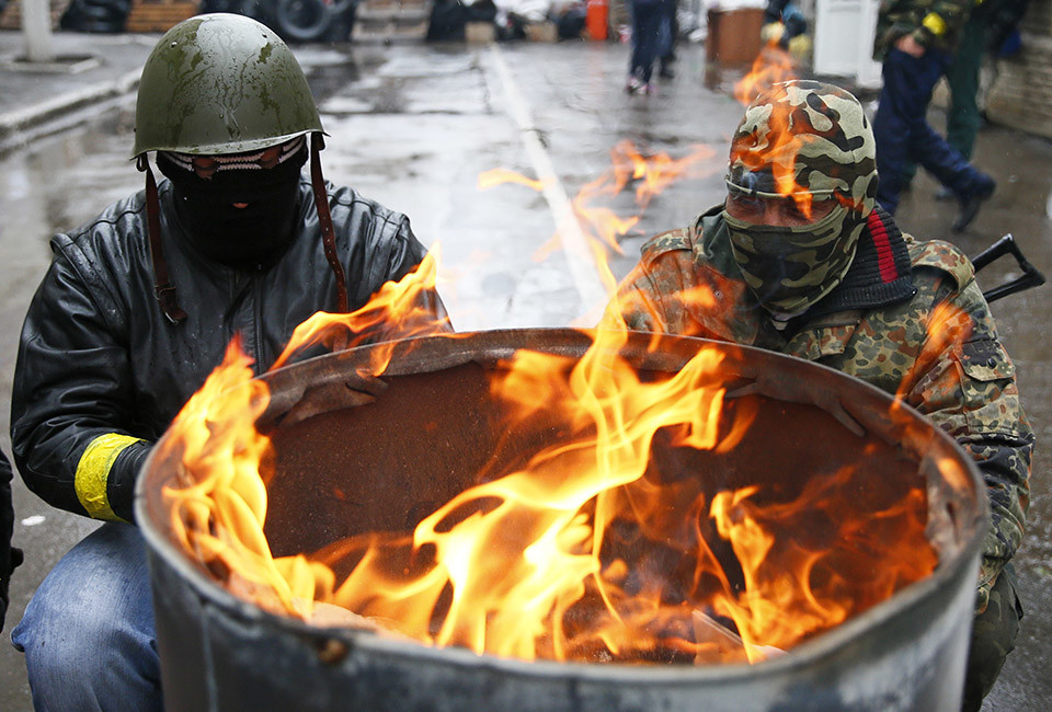 Pro-Russian men gather around a fire at a barricade near the police headquarters in Slaviansk April 13, 2014. One pro-Russian activist was killed in the east Ukrainian city of Slaviansk in clashes with forces loyal to the government in Kiev, Russian news agency RIA reported on Sunday, citing a local militant.