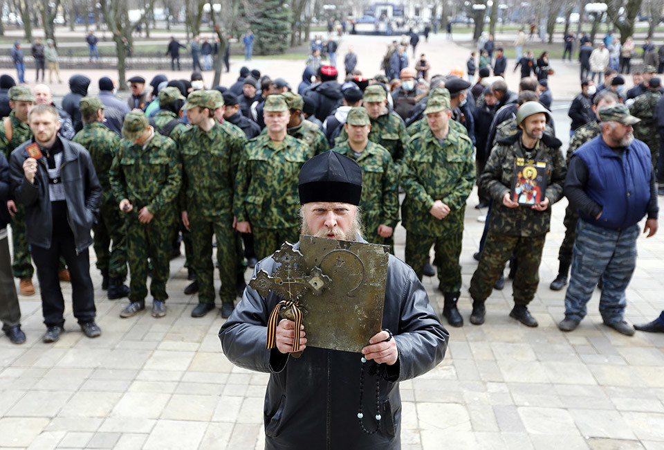 A man holds an icon and a cross as pro-Russian protesters gather in front of the regional administration headquarters in Luhansk, in eastern Ukraine April 14, 2014. Ukraine's president on Monday threatened military action after pro-Russian separatists occupying government buildings in the east ignored an ultimatum to leave and another group of rebels attacked a police headquarters in the troubled region.
