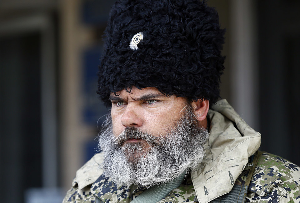 """A pro-Russian armed man looks on near the mayor's office in Slaviansk April 14, 2014. Towns in eastern Ukraine on Monday braced for military action from government forces as a deadline passed for pro-Russian separatists to disarm and end their occupation of state buildings or face a major """"anti-terrorist"""" operation."""