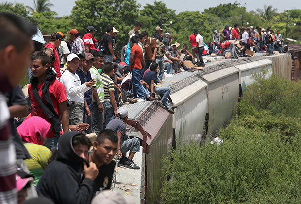 Central American immigrants arrive on top of a freight train on August 6, 2013 to Ixtepec, Mexico. Thousands of Central American migrants ride the trains, known as 'la bestia', or the beast, during their long and perilous journey north through Mexico to reach the United States border. Some of the immigrants are robbed and assaulted by gangs who control the train tops, while others fall asleep and tumble down, losing limbs or perishing under the wheels of the trains. Only a fraction of the immigrants who start the journey in Central America will traverse Mexico completely unscathed - and all this before illegally entering the United States and facing the considerable U.S. border security apparatus designed to track, detain and deport them.