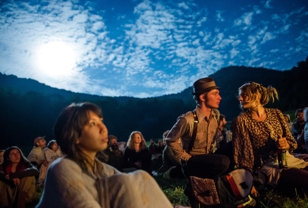A couple listens to a Raising Appalachia concert as the moon rises during the Firefly Gathering on the last night of the festival in 2013.