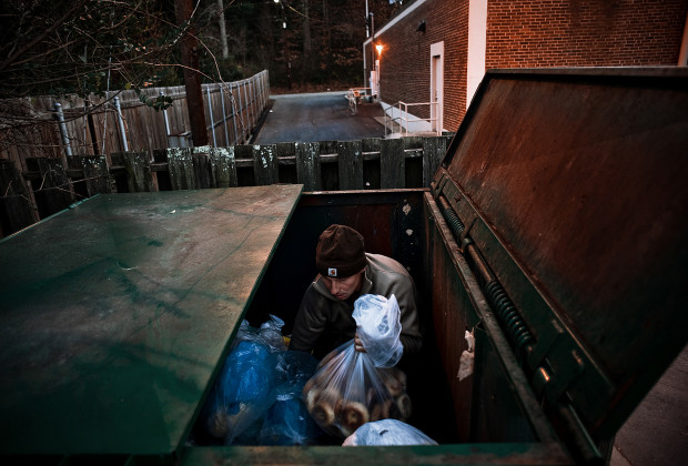 Misha pulls a full bag of bagels from a dumpster at Brugger's Bagels in Asheville, NC. When the Wildroots folks go out in the truck to dumpster, they can easily fill the entire truck bed with dumpstered food in an afternoon.
