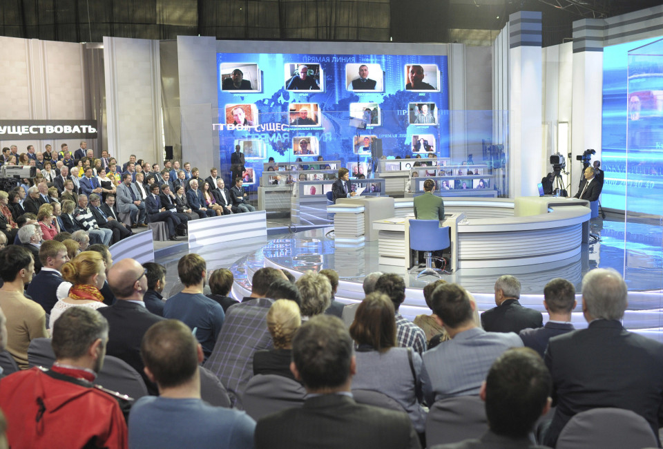 People attend Russian President Vladimir Putin's live broadcast nationwide phone-in in Moscow April 17, 2014. Putin on Thursday said Russia had been forced to respond to NATO enlargement and that its annexation of Crimea, home to its Black Sea Fleet, was partly influenced by the Western military alliance's expansion into eastern Europe