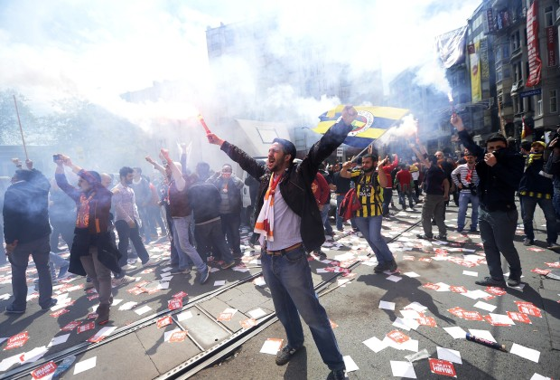 Galatasaray, Fenerbahce and Besiktas fan groups use flares as they protest against a new system of e-tickets on April 20, 2014, on Istiklal Avenue in Istanbul. A new system requiring Turkish football fans to buy special cards and electronic tickets to attend games in the stadiums has been implemented amid criticism and protests from the supporter groups. As of yesterday, anyone who wants to buy tickets for a football match in the Spor Toto Super League and PTT League One will be first asked to buy a card dubbed passolig, and the tickets for the games will be bought with this card. AFP PHOTO/BULENT KILIC        (Photo credit should read BULENT KILIC/AFP/Getty Images)