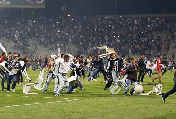 Besiktas fans throw plastic chairs onto the pitch during the Turkish Super League derby soccer match between Besiktas and Galatasaray at Ataturk Olympic Stadium in Istanbul late September 22, 2013. Hundreds of fans halted the Istanbul derby after storming the pitch at Istanbul's Olympic Stadium on Sunday, local media reported. Galatasaray were leading 2-1 in the third minute of added time when the match was halted, sending the players sprinting for the safety of the locker rooms. Picture taken September 22, 2013. REUTERS/Stringer (TURKEY - Tags: SPORT SOCCER CIVIL UNREST TPX IMAGES OF THE DAY) - RTX13WF0