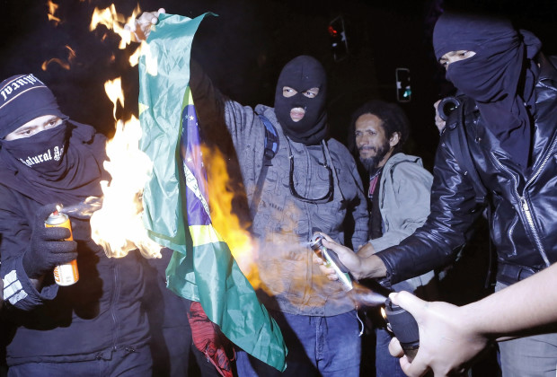 Demonstrators burn a Brazilian flag during a protest against the 2014 World Cup in Sao Paulo May 24, 2014. The demonstrators rallied against the hosting of the World Cup in Brazil, and the costs associated with the sporting event. Activists are demanding more money be spent on education, health care, public transportation and to fight crime.  REUTERS/Nacho Doce (BRAZIL - Tags: SPORT SOCCER CIVIL UNREST POLITICS WORLD CUP) - RTR3QPJO
