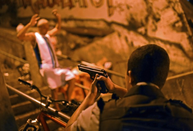 A Brazilian Police Special Forces member aims his gun as a man walks past with his arms up during a violent protest in a favela near Copacabana in Rio de Janeiro, Brazil on April 22, 2014. Violent protests broke out in Rio's landmark beachfront district, Copacabana, following the death of a resident last weekend during clashes with the Army in a nearby favela. AFP PHOTO / CHRISTOPHE SIMON        (Photo credit should read CHRISTOPHE SIMON/AFP/Getty Images)