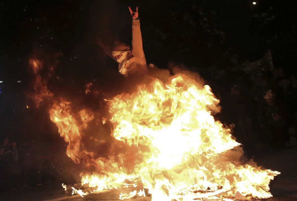 A demonstrator jumps over a burning barricade in the Marginal Pinheiros area during a protest against the 2014 World Cup, in Sao Paulo June 19, 2014.