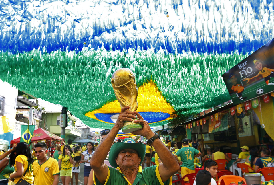 A man holds a model of the World Cup 2014 trophy ahead of the Brazil's World Cup soccer match against Mexico in Manaus June 17, 2014. In a project called ?On The Sidelines? Reuters photographers share pictures showing their own quirky and creative view of the 2014 World Cup in Brazil.