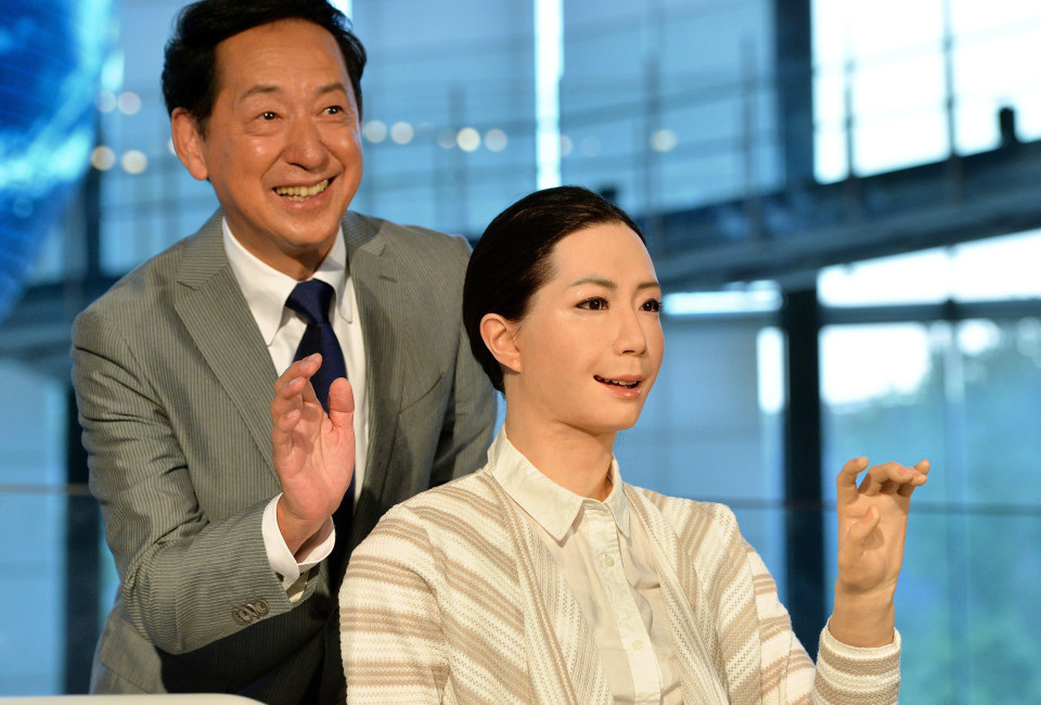 """Former astronaut and the director of the museum, Mamoru Mori (L), poses with a new female humanoid robot named """"Otonaroid"""" as she is introduced to the media at the National Museum of Emerging Science and Technology in Tokyo on June 24, 2014. Japanese scientists unveiled what they said was the world's first news-reading android, eerily lifelike and possessing a sense of humour to match her perfect language skills."""