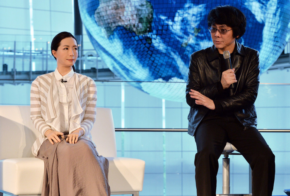 """Osaka University professor Hiroshi Ishiguro (R) introduces a new female humanoid robot named """"Otonaroid"""" to the media at the National Museum of Emerging Science and Technology in Tokyo on June 24, 2014. Japanese scientists unveiled what they said was the world's first news-reading android, eerily lifelike and possessing a sense of humour to match her perfect language skills."""