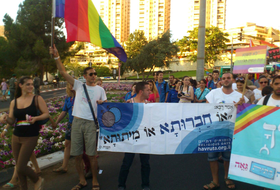 Daniel Jonas (left holding a flag) marching in pride parade holding a banner for the Hevruta organization.