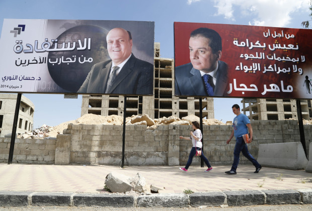 Election campaign posters for presidential candidate Maher Abdul-Hafiz Hajjar (R) and Hassan Abdallah al-Nouri are seen along a street in Damascus May 12, 2014. Assad will compete with other two candidates in a June presidential election, the Supreme Constitutional Court of Syria said on Saturday.  REUTERS/Omar Sanadiki (SYRIA - Tags: POLITICS CIVIL UNREST CONFLICT ELECTIONS) - RTR3OTPB