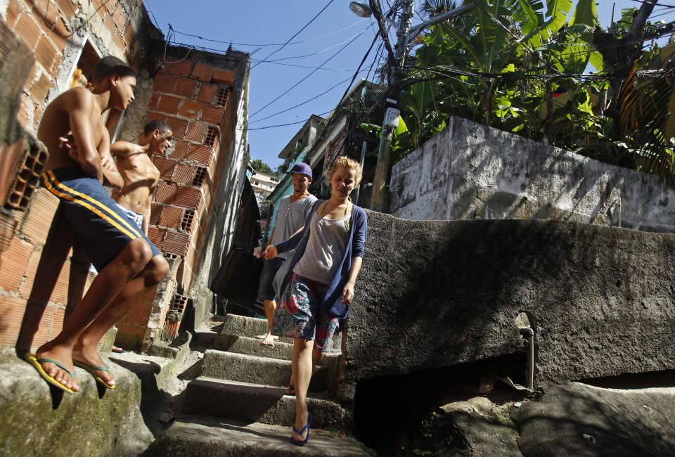 Young Woman walks past neighbours with her boyfriend, in the Vidigal slum in Rio de Janeiro .