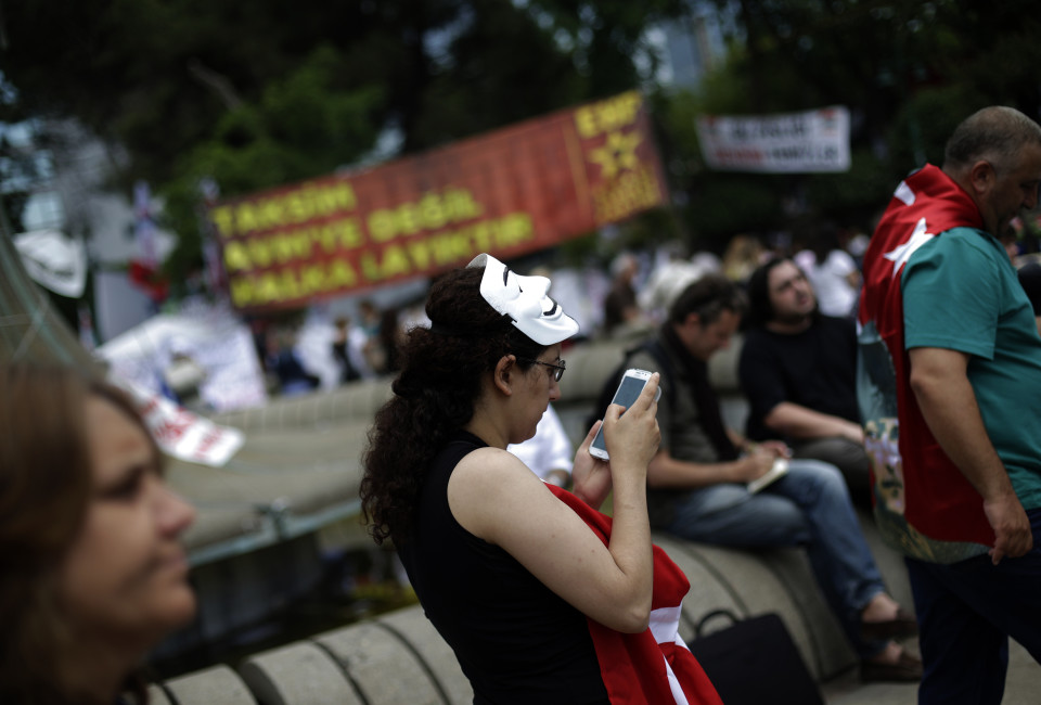 """A protester uses her mobile device as she walks at Gezi Park on Taksim Square in Istanbul June 6, 2013. The government has made clear its disapproval of social media services, which are being used more and more as newspapers and television come increasingly under the sway of the state. In a television interview last week, Prime Minister Tayyip Erdogan described sites such as Twitter as a """"scourge"""", saying they were used to spread lies about the government with the aim of terrorising society.   REUTERS/Stoyan Nenov (TURKEY  - Tags: CIVIL UNREST POLITICS) - RTX10DLU"""