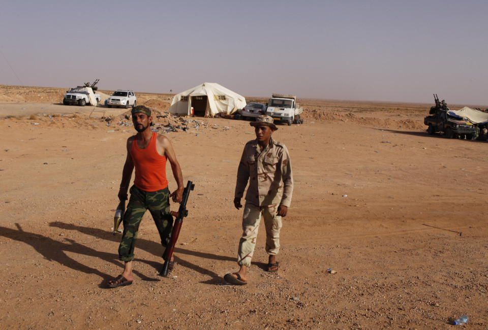 A rebel from Misrata carries a rocket-propelled grenade (RPG) as he walks at Bir Doufan checkpoint.
