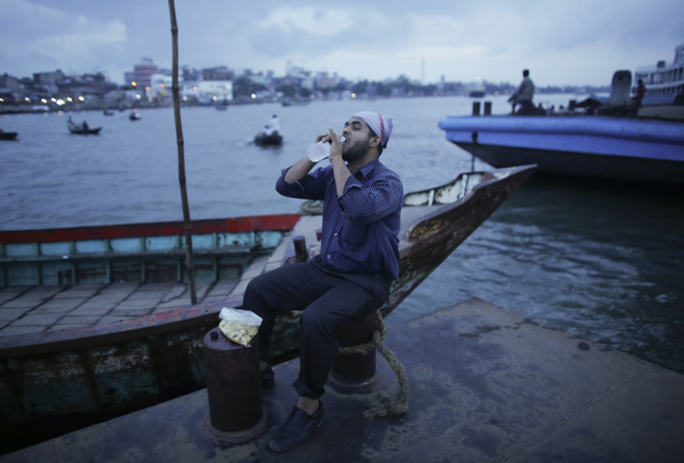A man drinks water as he breaks his fast by the river Buriganga during the holy month of Ramadan.
