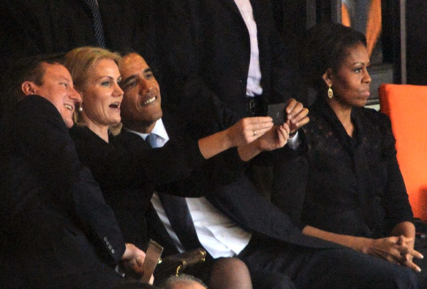 US President  Barack Obama (R) and British Prime Minister David Cameron pose for a selfie picture with Denmark's Prime Minister Helle Thorning Schmidt (C) next to US First Lady Michelle Obama (R) during the memorial service of South African former president Nelson Mandela at the FNB Stadium (Soccer City) in Johannesburg on December 10, 2013. Mandela, the revered icon of the anti-apartheid struggle in South Africa and one of the towering political figures of the 20th century, died in Johannesburg on December 5 at age 95.   AFP PHOTO / ROBERTO SCHMIDT        (Photo credit should read ROBERTO SCHMIDT/AFP/Getty Images)