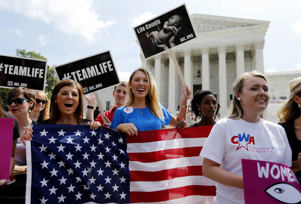 Anti-abortion protestors celebrate the U.S. Supreme Court's ruling striking down a Massachusetts law that mandated a protective buffer zone around abortion clinics, as the demonstrators stand outside the Court  in Washington June 26, 2014. On a 9-0 vote, the court said the 2007 law violated the freedom of speech rights of anti-abortion protesters under the First Amendment of the U.S. Constitution in preventing them from standing on the sidewalk and speaking to people entering the clinics.