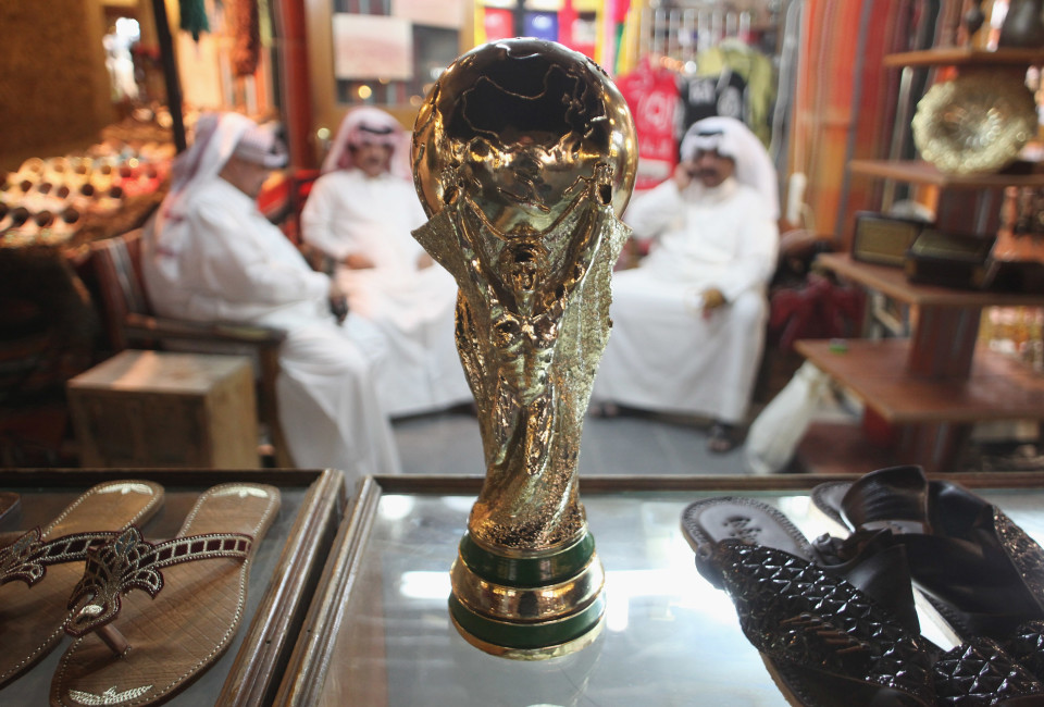 Arab men sit at a shoemaker's stall with a replica of the FIFA World Cup trophy in the Souq Waqif traditional market in Doha, Qata.