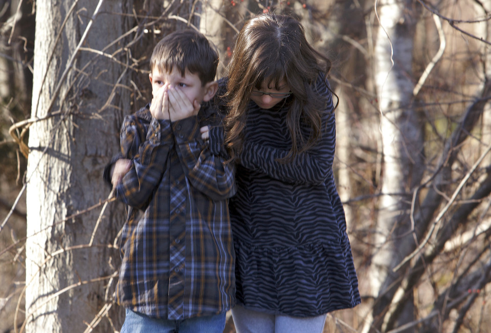 First-grader Henry Terifay and his sister, fourth-grader Kelly Terifay, wait outside Sandy Hook Elementary School after a shooting in Newtown, Connecticut, December 14, 2012. A shooter opened fire at the elementary school. REUTERS/Michelle McLoughlin (UNITED STATES - Tags: CRIME LAW EDUCATION TPX IMAGES OF THE DAY) - RTR3BKQ7