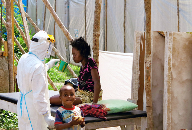 A health worker, wearing head-to-toe protective gear, offers water to a woman with Ebola, at a treatment centre for infected persons, as a young boy stands nearby in Kenema Government Hospital, in Kenema, Eastern Province, Sierra Leone, in this handout photo courtesy of UNICEF taken in July 2014.  The death toll from the Ebola outbreak in West Africa has risen to 1,350, the World Health Organization said on August 20, 2014, with 106 new deaths reported between August 17-18 in three countries.