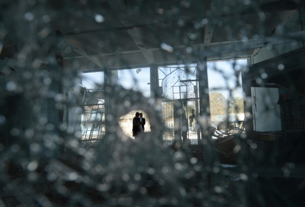 Afghan men are seen through bullet-shattered glass at the scene of the September 4 suicide attack on a government compound in Ghazni, during a media tour of the area on September 13, 2014. A Taliban attack September 4 on a government compound killed 13 security personnel and left at least 60 other people wounded when a truck bomb triggered hours of fighting, officials said. About 20 insurgents armed with machine guns and grenade launchers were also killed during the assault on the intelligence agency base in Ghazni province, one of the most volatile regions of Afghanistan. AFP PHOTO/SHAH Marai        (Photo credit should read SHAH MARAI/AFP/Getty Images)